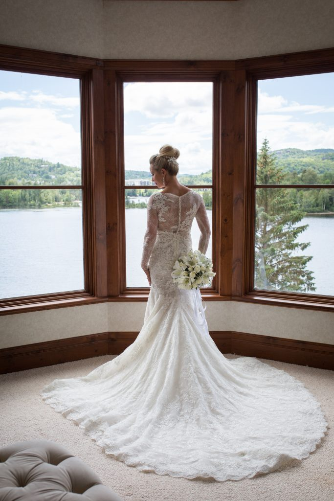 Montreal wedding photographer at hotel Quintessence bride in window facing lake tremblant