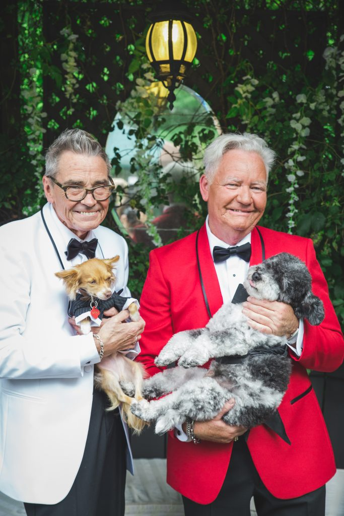 groom and groom with their dogs in tuxedos