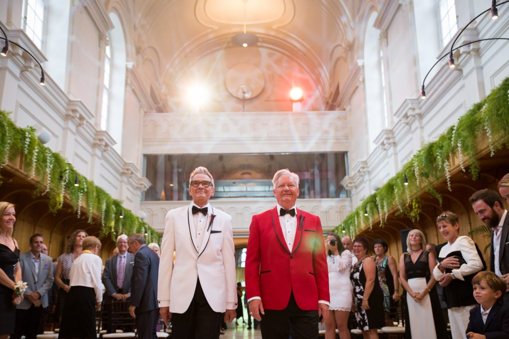 Groom and groom walking down the aisle at their wedding ceremony