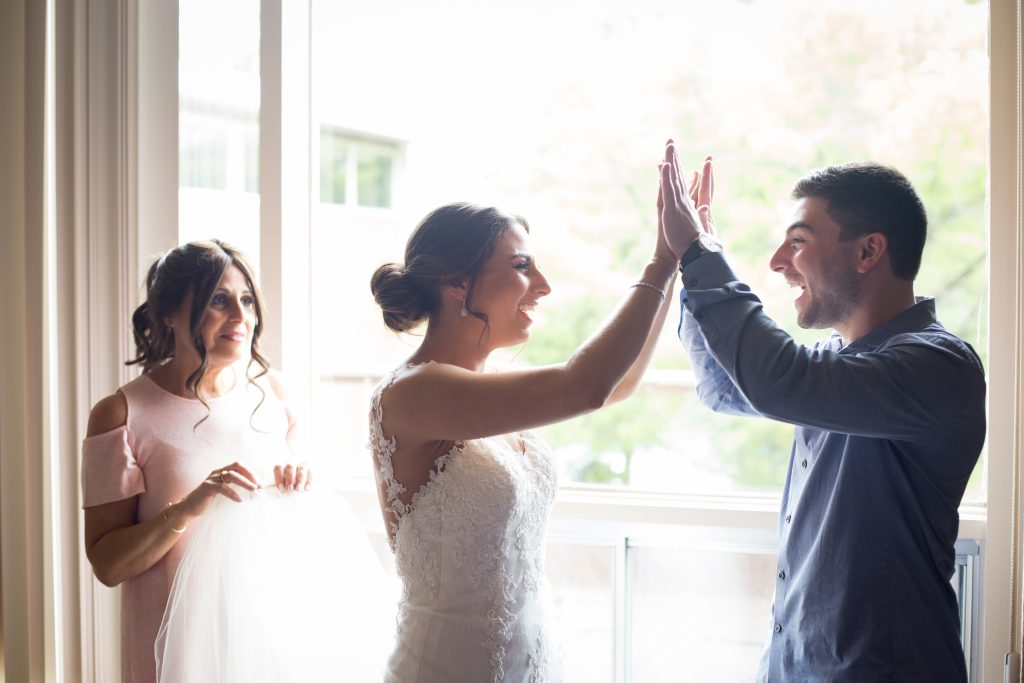 Bride and brother of the bride, giving each other high fives on her wedding day while the mother of the bride watches