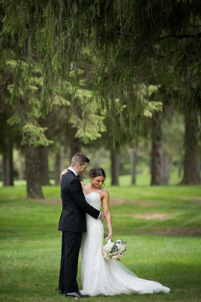 Bride and groom portrait in the forest with greenery all around them in Montreal