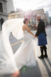Photography in Montreal of bride and groom standing in the street with sun through wedding veil