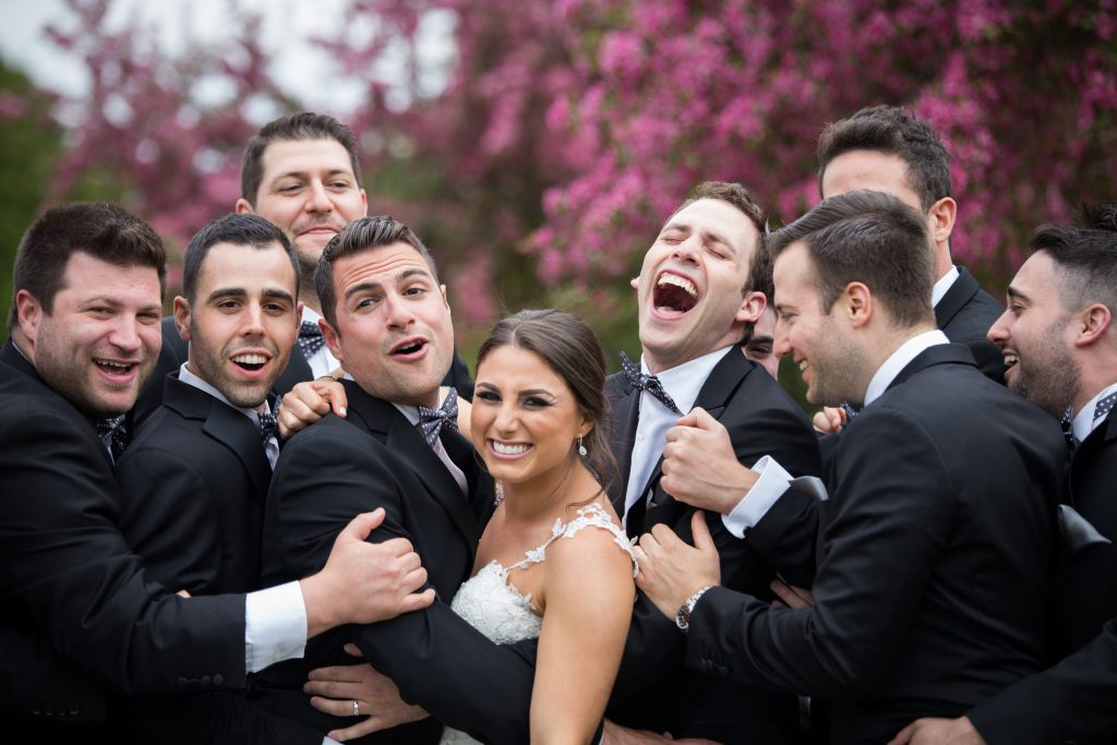 Bride surrounded by groomsmen outside on her wedding day
