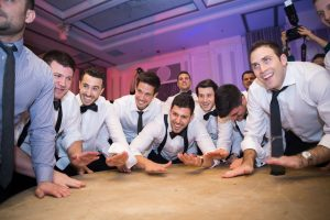 Jewish wedding groomsmen during the horrah