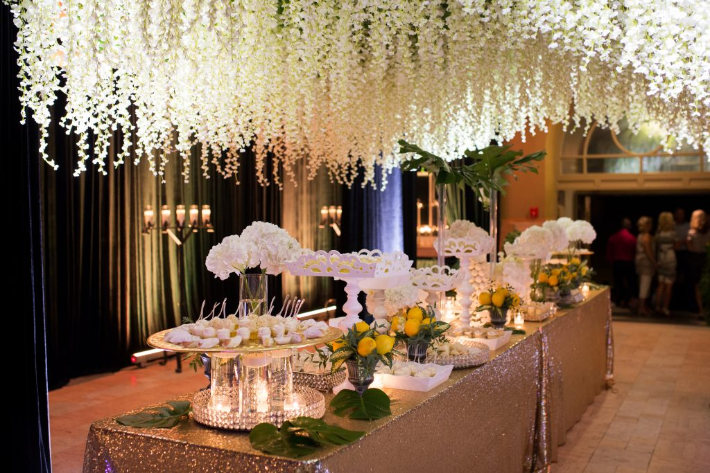Sweet table under cascading white flowers from the ceiling with gold table cloth