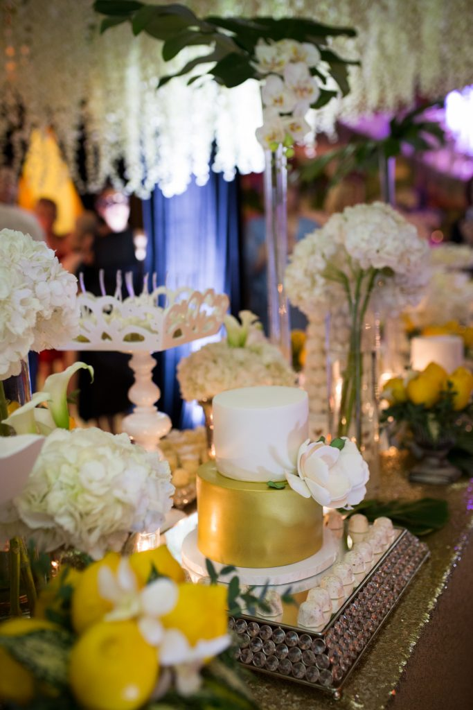 sweet table with mini wedding cake sourrounded by white flowers greenery and lemons with gold table cloth