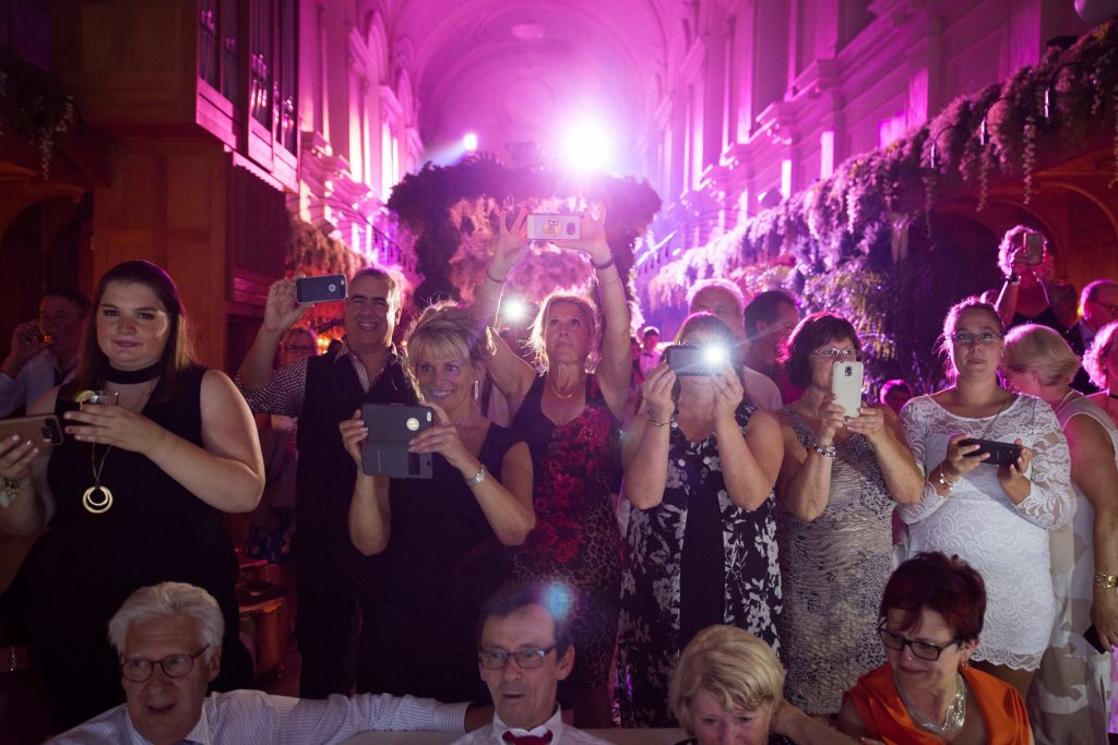 Wedding guests taking pictures with their cellphones at a wedding reception, abbaye, oka