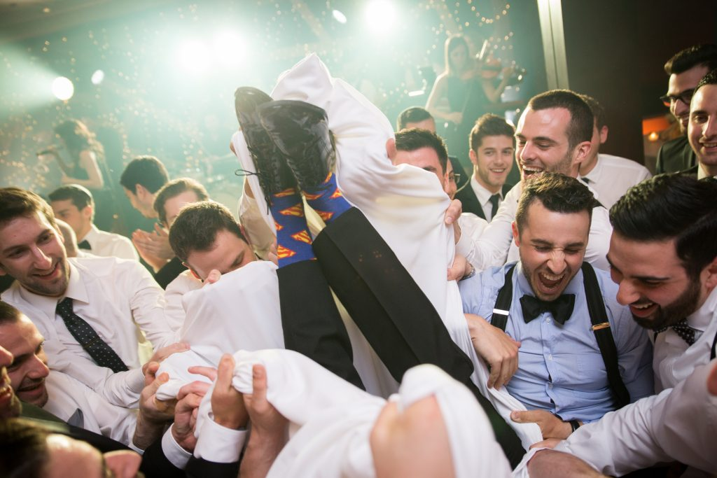 Groom with superman socks surrounded by groomsmen in the horah