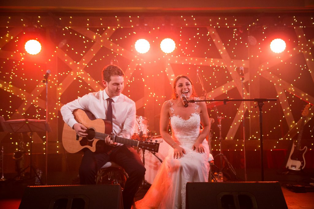 Bride singing to her groom on stage for her wedding day in Montreal