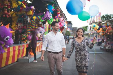 A couple holding balloons at a carnival